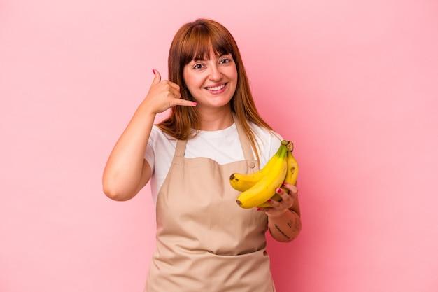 분홍색 배경에 격리된 바나나를 들고 집에서 요리하는 백인 매력적인 여성은 손가락으로 휴대폰 통화 제스처를 보여줍니다.
