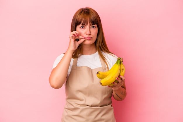 秘密を保持している唇に指でピンクの背景に分離されたバナナを保持している自宅で調理している若い白人の曲がりくねった女性。