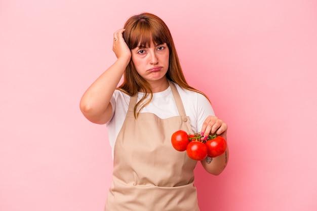 ピンクの背景に分離されたトマトを持って家で料理をしている若い白人の曲線美の女性はショックを受けて、彼女は重要な会議を思い出しました。