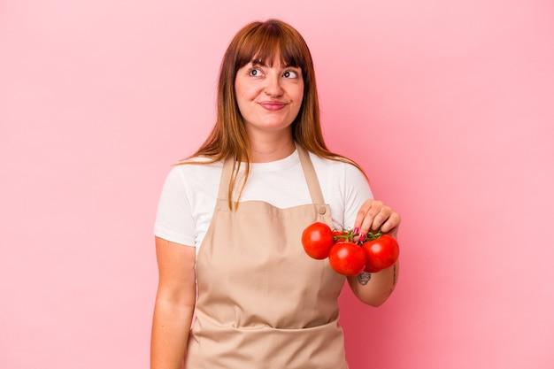目標と目的を達成することを夢見てピンクの背景に分離されたトマトを保持している自宅で料理をする若い白人の曲がりくねった女性