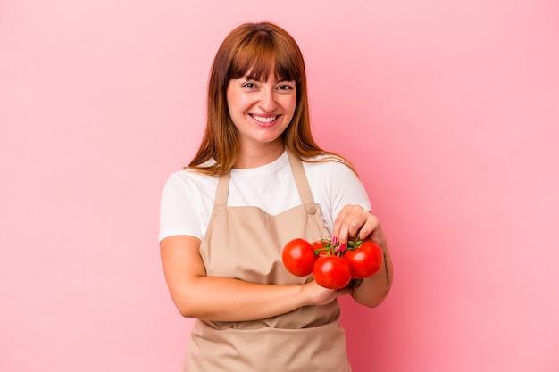 笑って楽しんでピンクの背景に分離されたトマトを持って自宅で料理をしている若い白人の曲がりくねった女性。
