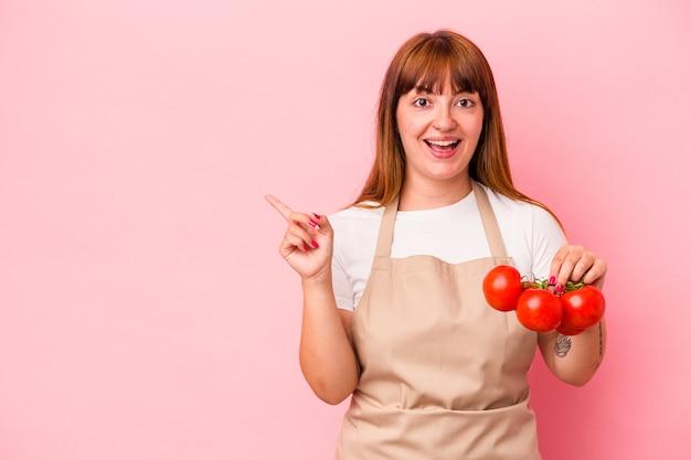 ピンクの背景に分離されたトマトを持って家で料理をしている若い白人の曲線美の女性は、笑顔で脇を指して、空白のスペースで何かを示しています。