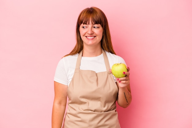 Young caucasian curvy woman cooking at home holding an apple isolated on pink background looks aside smiling, cheerful and pleasant.