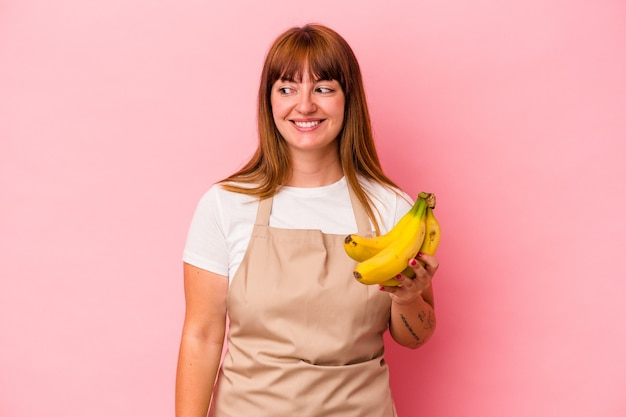 Young caucasian curvy woman cooking at home holding bananas isolated on pink background looks aside smiling, cheerful and pleasant.