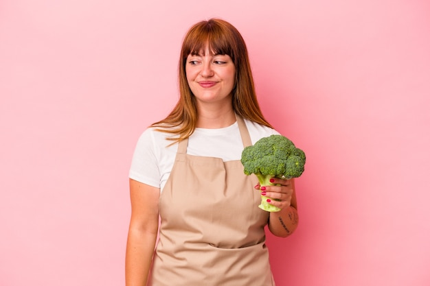 Young caucasian curvy woman cooking at home holding broccoli  isolated on pink background looks aside smiling, cheerful and pleasant.