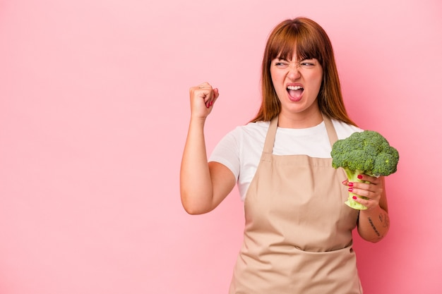 Young caucasian curvy woman cooking at home holding broccoli  isolated on pink background raising fist after a victory, winner concept.