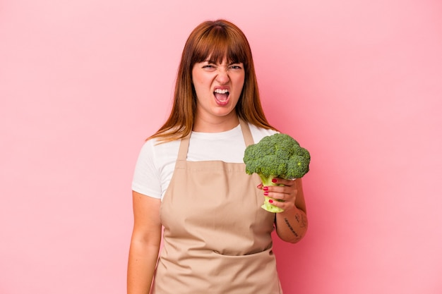 Young caucasian curvy woman cooking at home holding broccoli  isolated on pink background screaming very angry and aggressive.
