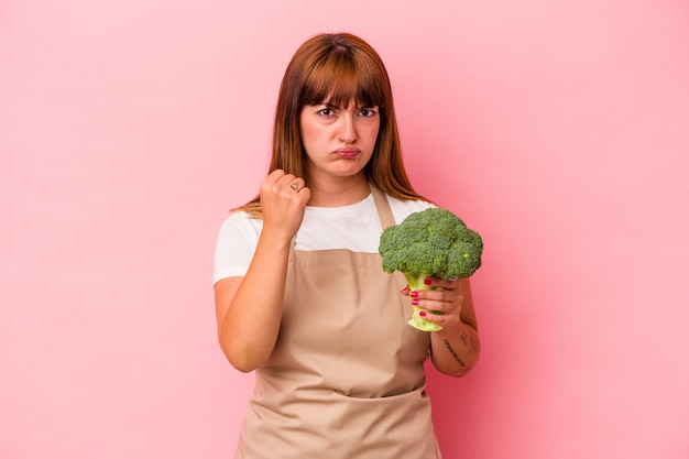 Young caucasian curvy woman cooking at home holding broccoli  isolated on pink background showing fist to camera, aggressive facial expression.