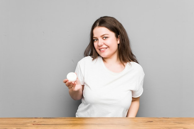 회색 벽에 고립 된 로션을 들고 젊은 백인 매력적인 여자