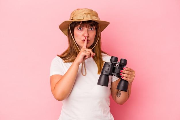 분홍색 배경에 고립된 쌍안경을 들고 비밀을 유지하거나 침묵을 요구하는 젊은 백인 매력적인 여성.