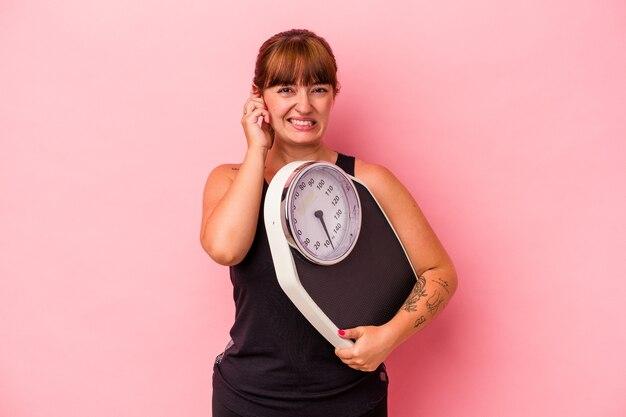 手で耳を覆うピンクの背景に分離された計量機を保持している若い白人の曲線美の女性。