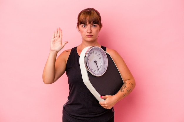 ピンクの背景に分離された計量機を保持している若い白人の曲線美の女性は、一時停止の標識を示している手を伸ばして立って、あなたを防ぎます。