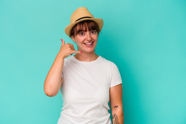Young caucasian curvy woman isolated on blue background showing a mobile phone call gesture with fingers.