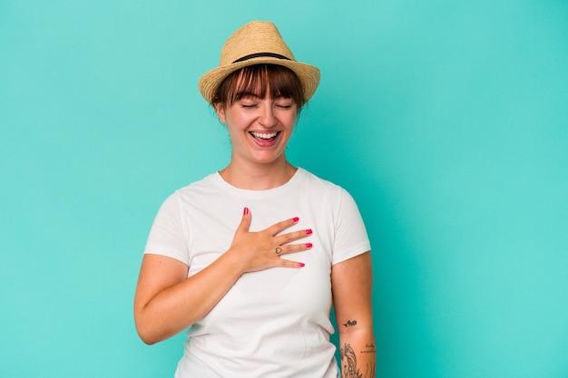 青い背景に分離された若い白人の曲線美の女性は、胸に手を置いて大声で笑います。