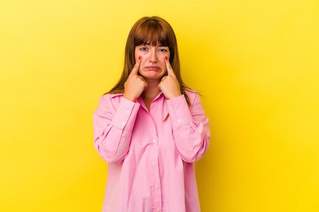 Молодая кавказская соблазнительная женщина изолирована на желтом фоне плачет, недовольна чем-то, агонией и концепцией замешательства.