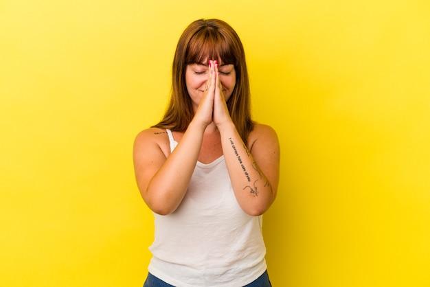 口の近くで祈って手をつないで黄色の背景に分離された若い白人の曲線美の女性は、自信を持っています。