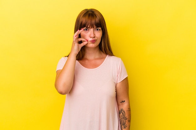 秘密を保持している唇に指で黄色の背景に分離された若い白人の曲線美の女性。