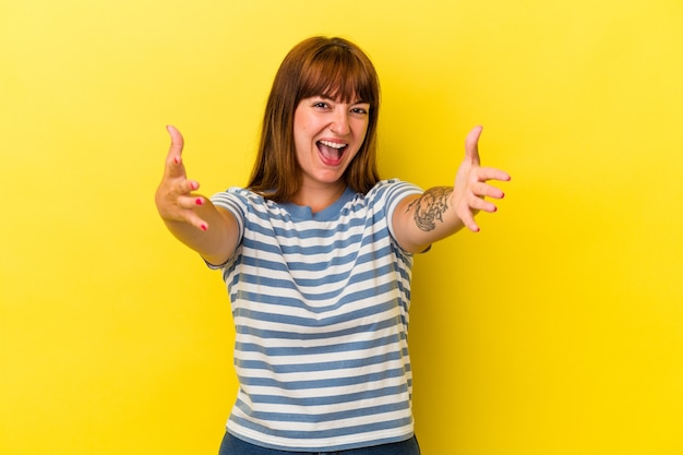 Young caucasian curvy woman isolated on yellow background feels confident giving a hug to the camera.