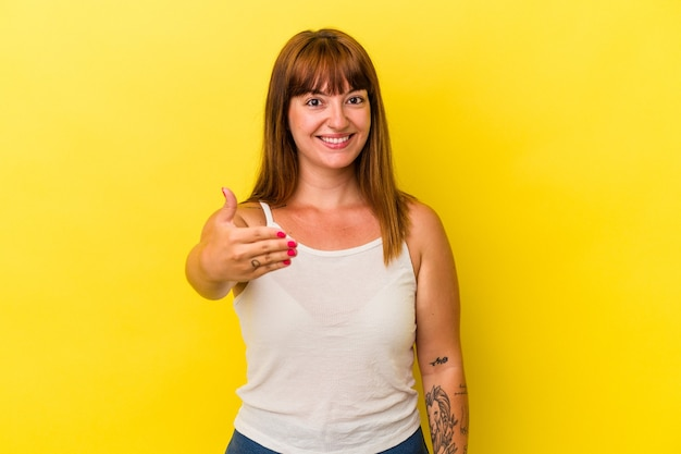 Young caucasian curvy woman isolated on yellow background stretching hand at camera in greeting gesture.
