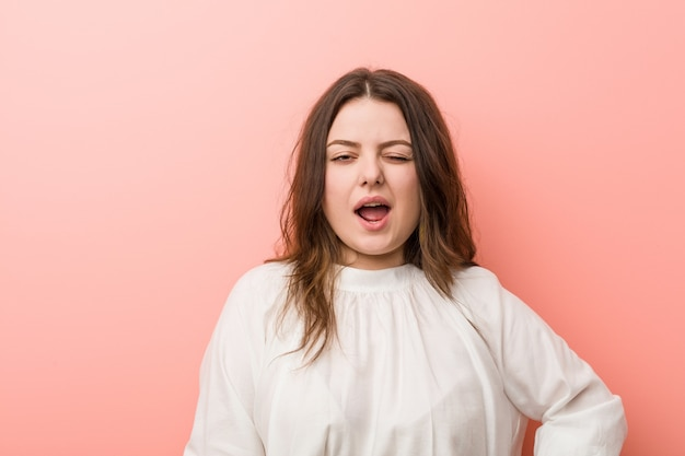 Young caucasian curvy woman standing against pink background