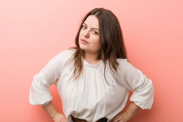 Young caucasian curvy woman standing against pink wall