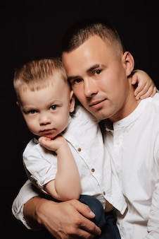 Young caucasian dad and boy son in white shirts pose on black space