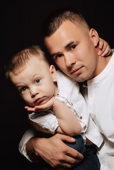 Young caucasian dad and boy son in white shirts posing
