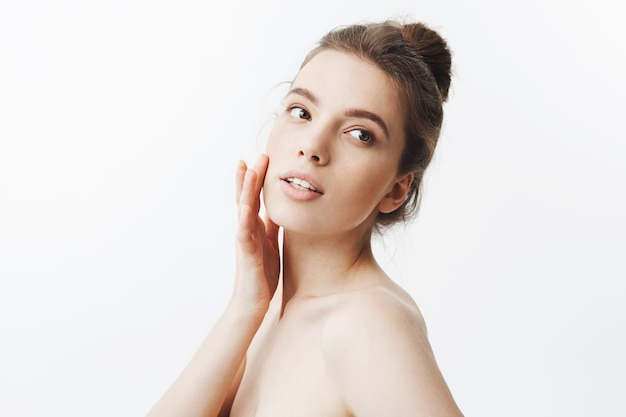 Young caucasian dark-haired student girl with bun hairstyle and naked body touching skin on face with fingers, lookin aside with calm and relaxed face expression.