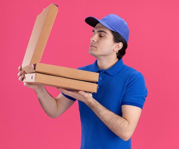 Молодой кавказский доставщик в синей форме и кепке держит упаковки с пиццей, открывая одну и обнюхивая ее с закрытыми глазами