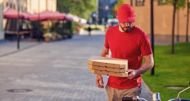 Молодой кавказский доставщик в красной форме, доставляющий пиццу, стоя возле своего скутера, селективный фокус на курьера. концепция доставки еды