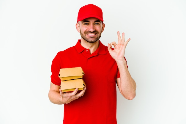 Young caucasian delivery man isolated on white wall cheerful and confident showing ok gesture.
