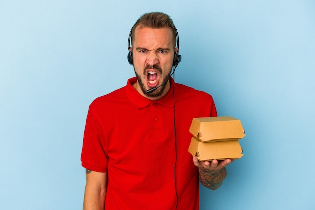 Young caucasian delivery man with tattoos holding burgers isolated on blue background  screaming very angry and aggressive.