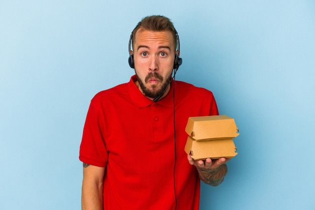 Young caucasian delivery man with tattoos holding burgers isolated on blue background  shrugs shoulders and open eyes confused.