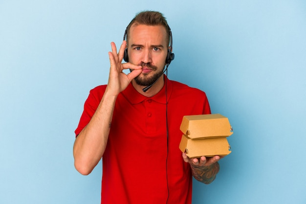 Young caucasian delivery man with tattoos holding burgers isolated on blue background  with fingers on lips keeping a secret.
