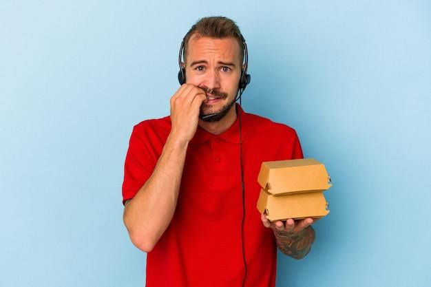 青い背景に隔離されたハンバーガーを保持している入れ墨を持つ若い白人配達人は、神経質で非常に心配している。