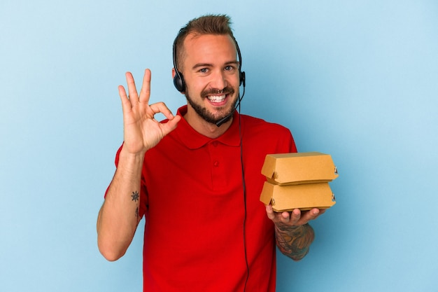 青い背景に分離されたハンバーガーを保持している入れ墨を持つ若い白人配達人は陽気で自信を持って大丈夫なジェスチャーを示しています。