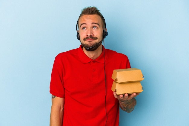 目標と目的を達成することを夢見て青い背景に分離されたハンバーガーを保持している入れ墨を持つ若い白人配達人