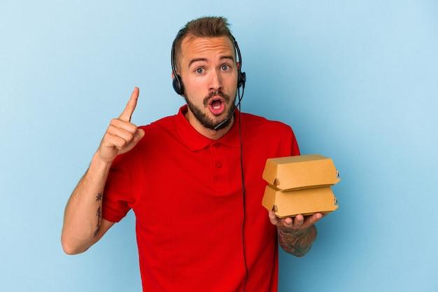 アイデア、インスピレーションの概念を持っている青い背景に分離されたハンバーガーを保持している入れ墨を持つ若い白人配達人。