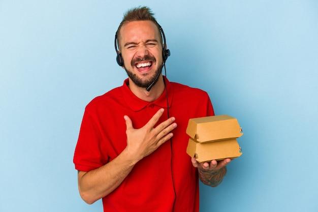 Молодой кавказский курьер с татуировками, держащий гамбургеры, изолированные на синем фоне, громко смеется, держа руку на груди.