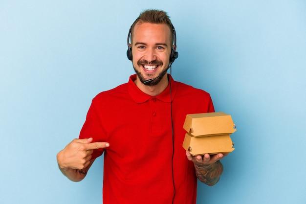 誇りと自信を持って、シャツのコピースペースを手で指している青い背景の人に分離されたハンバーガーを保持している入れ墨を持つ若い白人配達人