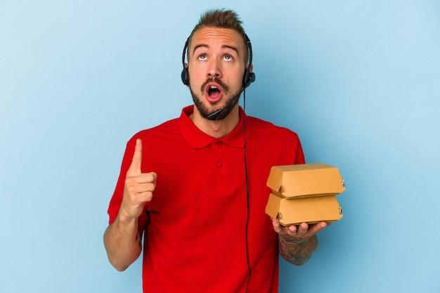 開いた口で逆さまを指している青い背景に分離されたハンバーガーを保持している入れ墨を持つ若い白人配達人。
