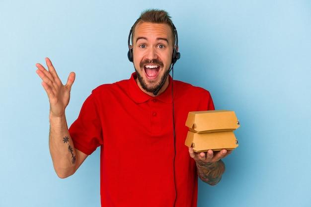 青い背景に分離されたハンバーガーを保持している入れ墨を持つ若い白人配達人は、嬉しい驚きを受け取り、興奮し、手を上げます。