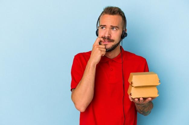 青い背景に分離されたハンバーガーを保持している入れ墨を持つ若い白人配達人は、コピースペースを見ている何かについて考えてリラックスしました。