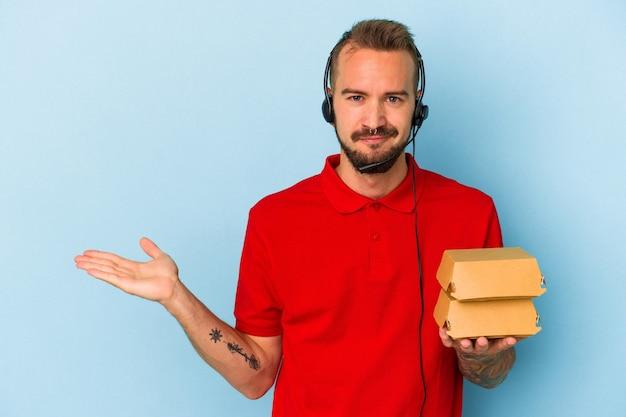 手のひらにコピースペースを示し、腰に別の手を保持している青い背景に分離されたハンバーガーを保持している入れ墨を持つ若い白人配達人。