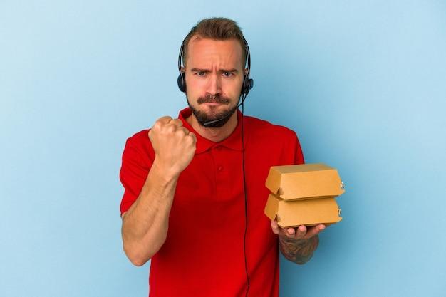 カメラに拳、攻撃的な表情を示す青い背景に分離されたハンバーガーを保持している入れ墨を持つ若い白人配達人。
