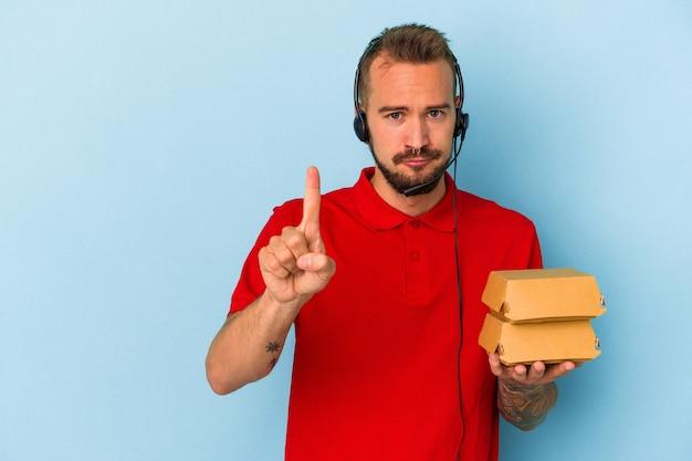 指でナンバーワンを示す青い背景で隔離のハンバーガーを保持している入れ墨を持つ若い白人配達人。
