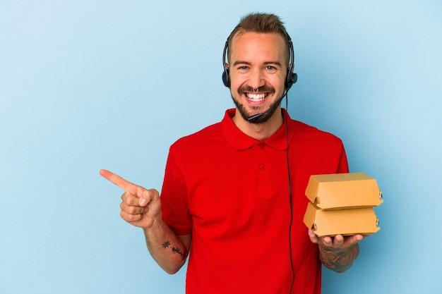 青い背景に分離されたハンバーガーを保持している入れ墨を持つ若い白人配達人は、笑顔で脇を指して、空白のスペースで何かを示しています。