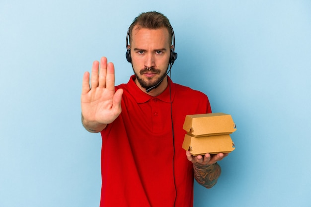 青い背景に分離されたハンバーガーを保持している入れ墨の若い白人配達人は、一時停止の標識を示している手を伸ばして立って、あなたを防ぎます。