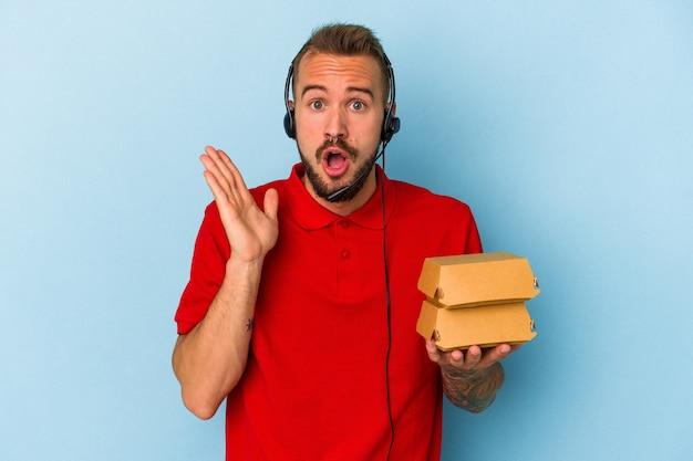 青い背景に分離されたハンバーガーを保持している入れ墨を持つ若い白人配達人は驚いてショックを受けました。