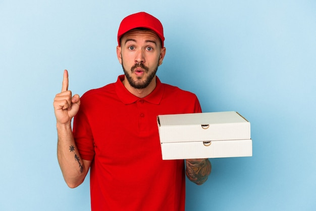 Young caucasian delivery man with tattoos holding pizzas isolated on blue background  having some great idea, concept of creativity.
